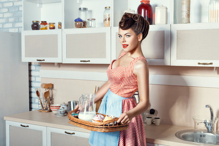 Woman holding a tray with dessert, she in the kitchen wearing an apron. Stok Fotoğraf