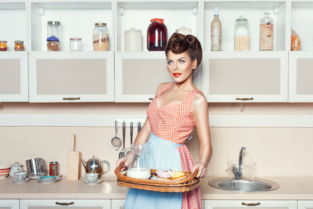Girl with Cake and milk standing in the kitchen. photo