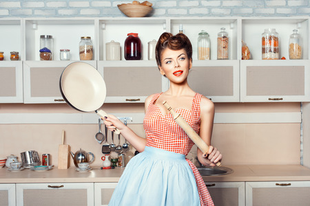 The girl in the kitchen in the hands holding pan and rolling pin. Фото со стока