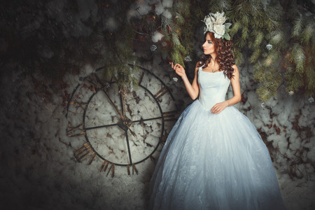 Woman with flowers on her head in the fairy forest, behind her big clock.