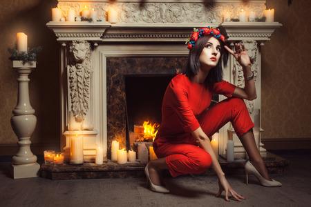 25cf5e3e64f3 La chica con un mono rojo se sentó cerca de la chimenea y que presenta  cerca de velas encendidas.