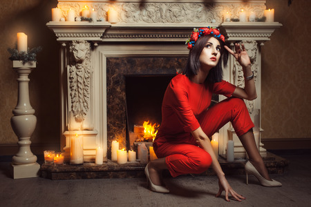 The girl in red overalls sat near the fireplace and posing near burning candles.