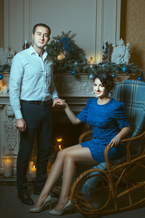 blessedness: The man holding the hand of a woman who is sitting in a chair near the fireplace, in terms of burning candles.