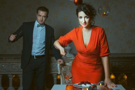 threatens: Woman in red dress threatens a fork, a man behind her is out of focus, in the hands of a knife.
