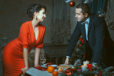 despite: A man in a suit and woman in red dress looking at each other in the eye and smile.