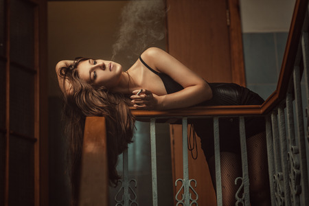 Woman blowing smoke lying on the railing at an stairwell. photo