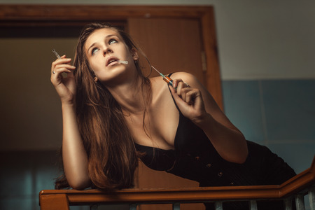 dead woman: Woman with a cigarette and syringe taking drugs in the stairwell. Stock Photo