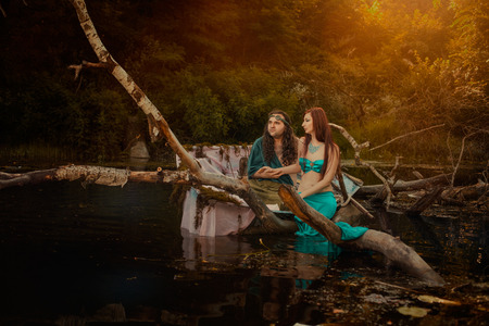 seamaid: Fabulous mythological man and woman sitting in a swamp, they love.