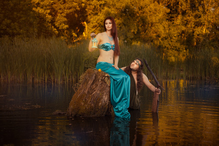 seamaid: Fairytale sad woman sitting on a stump in the marshes, in the back looks fabulous man. Stock Photo