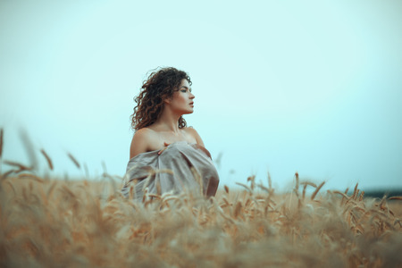 blessedness: Sexy girl portrait in profile in a field of wheat. Stock Photo