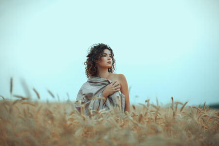 beatitude: Girl stands in a field with a cloth lightly close.