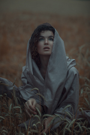 beatitude: Close portrait of a girl in a field that looks up in the darkest colors.