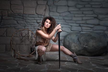 espadas medievales: La chica se sent� apoyado en una espada que Amazon vestido con pieles. Foto de archivo