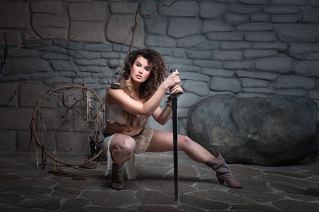 The girl sat leaning on a sword she Amazon dressed in skins.
