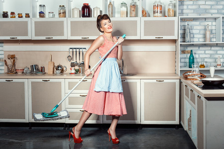 Happy girl makes cleaning the kitchen, hands holding a mop while singing.