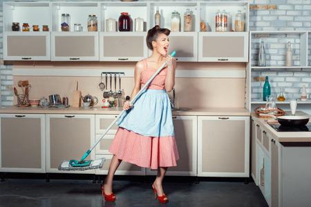 La jeune fille ouvrit la bouche beaucoup parce que quand elle chante nettoie la cuisine. Elle portait un balai pour laver les planchers. Banque d'images - 35466927