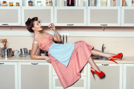 Woman lay on the kitchen table and flirting eats cake. On her feet with a large red shoes heel.