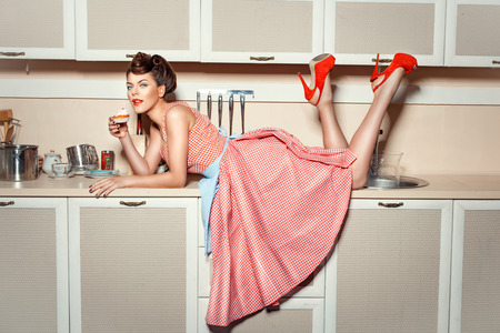 the high: Girl in red shoes climbed on the kitchen table and eat cake.