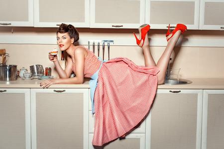 high: Muchacha en zapatos rojos se subió a la mesa de la cocina y comer pastel.