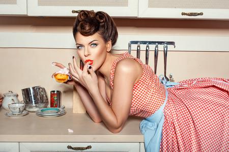 cocina antigua: Ni�a comiendo pastel y lamiendo sus dedos, ella estaba acostada sobre la mesa.
