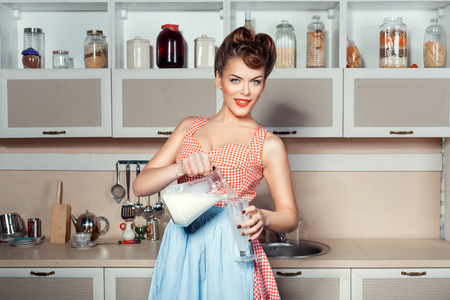 The girl in the kitchen holding a pitcher from which pours milk into a glass. Фото со стока