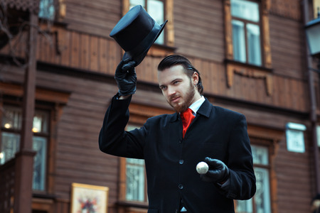 Man in retro style is on the street in his hand headdress cylinder. Stock Photo