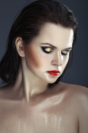 Close portrait of a girl with wet skin and bright makeup, gold on the eyelids.