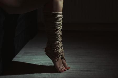 sadism: Beautiful legs tied with rope in bondage. Photo toning.