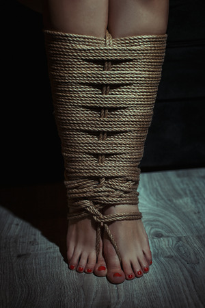 bondage: Close-up, legs openwork associated with a rope. Photo toned. Stock Photo