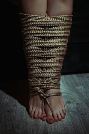 pies sexis: Primer plano, piernas calado asociado con una cuerda. Foto entonada. Foto de archivo