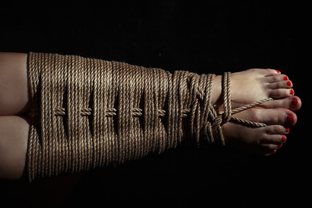 Female legs tied with a rope with a pattern. Photo toned.