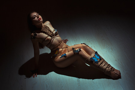 Beautiful woman sitting on the floor naked, her pattern of ropes as the art of shibari. Photo Artistic toned. Stock Photo