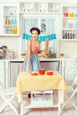 Pin-up girl style. Retro girl standing in the kitchen with a rolling pin for the dough in his hands. Stok Fotoğraf