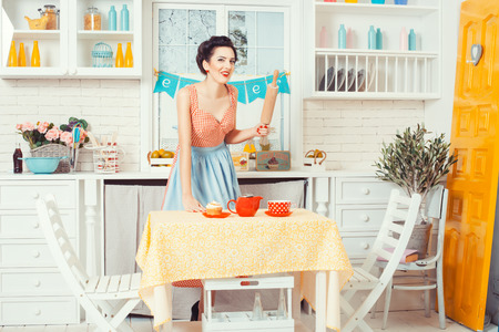 footsie: Pin-up girl style. Girl standing in the kitchen and smiles, in hands holds a rolling pin for the dough.
