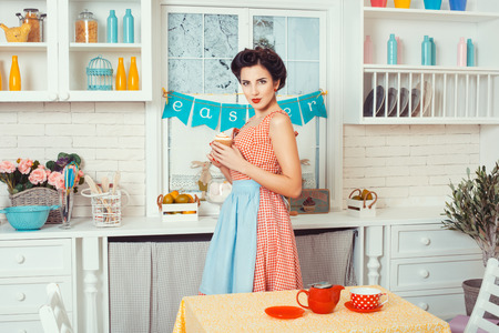 retro housewife: Pin-up girl style. Girl standing in the kitchen and holding muffins.