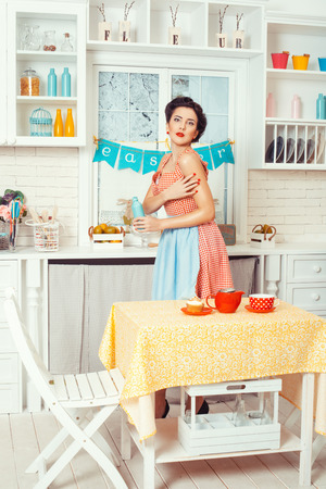 footsie: Pin-up girl style. Girl in retro style stands in the kitchen and holding a bottle.