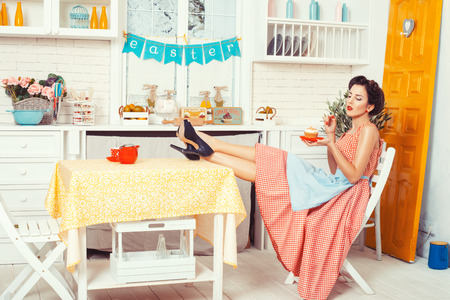 Pin-up girl style. Girl sitting on a chair at the table, in the hands holding a muffin. Фото со стока