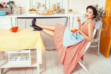 Pin-up girl style. Girl sitting in the kitchen to put his feet on the table, hands holding a muffin.