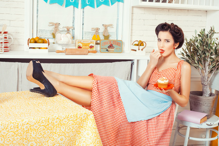 Pin-up girl style. In the kitchen, sitting on a chair girl and her legs laid on the table, hands holding a muffin. 写真素材