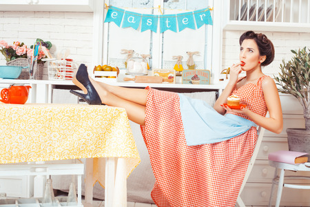 footsie: Pin-up girl style. The kitchen sits a girl, but in the hands holding a muffin with cream. Her mouth finger.