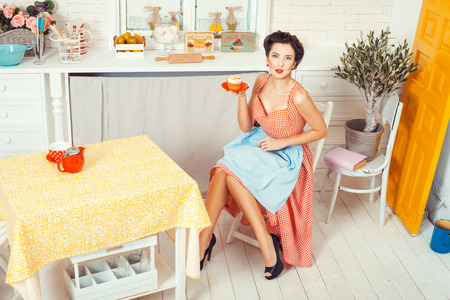 Pin-up girl style. The view from the top. Girl sitting on the middle of the kitchen and holding a saucer muffin.