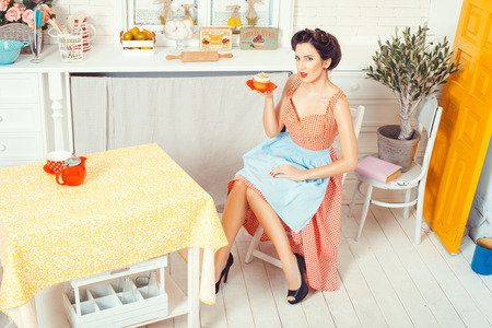 footsie: Pin-up girl style. The view from the top. Woman in an apron sitting on a chair in the middle of the kitchen and holding a saucer with muffin.