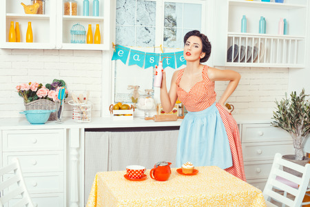 sexy funny: Pin-up girl style. Girl standing in the kitchen and holding a bottle of drink. Stock Photo