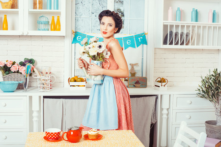 footsie: Pin-up girl style. Girl standing in the kitchen and holding a vase in which the flowers.
