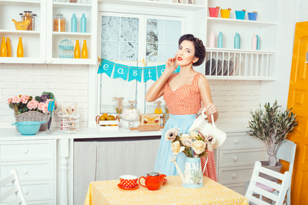 Pin-up style. Girl watering flowers standing in the kitchen in a retro style. Фото со стока
