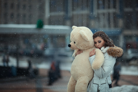 City, snowing, there is a girl with a toy bear in hands and presses it to her. The background blured and can not be read. Photo toned.