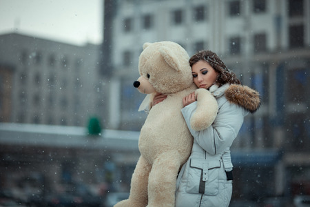 Mull: Girl in winter during snowfall is in the city. She cuddle toy bear, her eyes closed and a sad face. Photo with open aperture and soft focus. Photo toned.