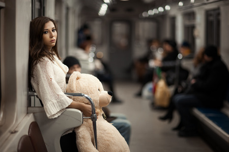 lamentable: Sad girl with toy bear in her hands, she in a subway car. Rear people but they are very vague and can not be found. Photo toned.
