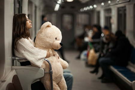 Sad girl hugged her toy bear and riding in a subway car. The background blured, people are not recognizable. Photographs of the executed on the open aperture with a soft focus. Photo toned.