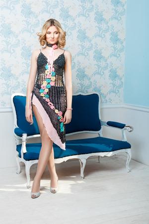 gambe aperte: Ragazza in piedi nella stanza con gli occhi sul pavimento. Il suo bel vestito all'uncinetto con le gambe aperte, scarpe ai piedi. Archivio Fotografico